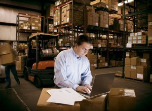 Man Working on a Laptop in a Warehouse